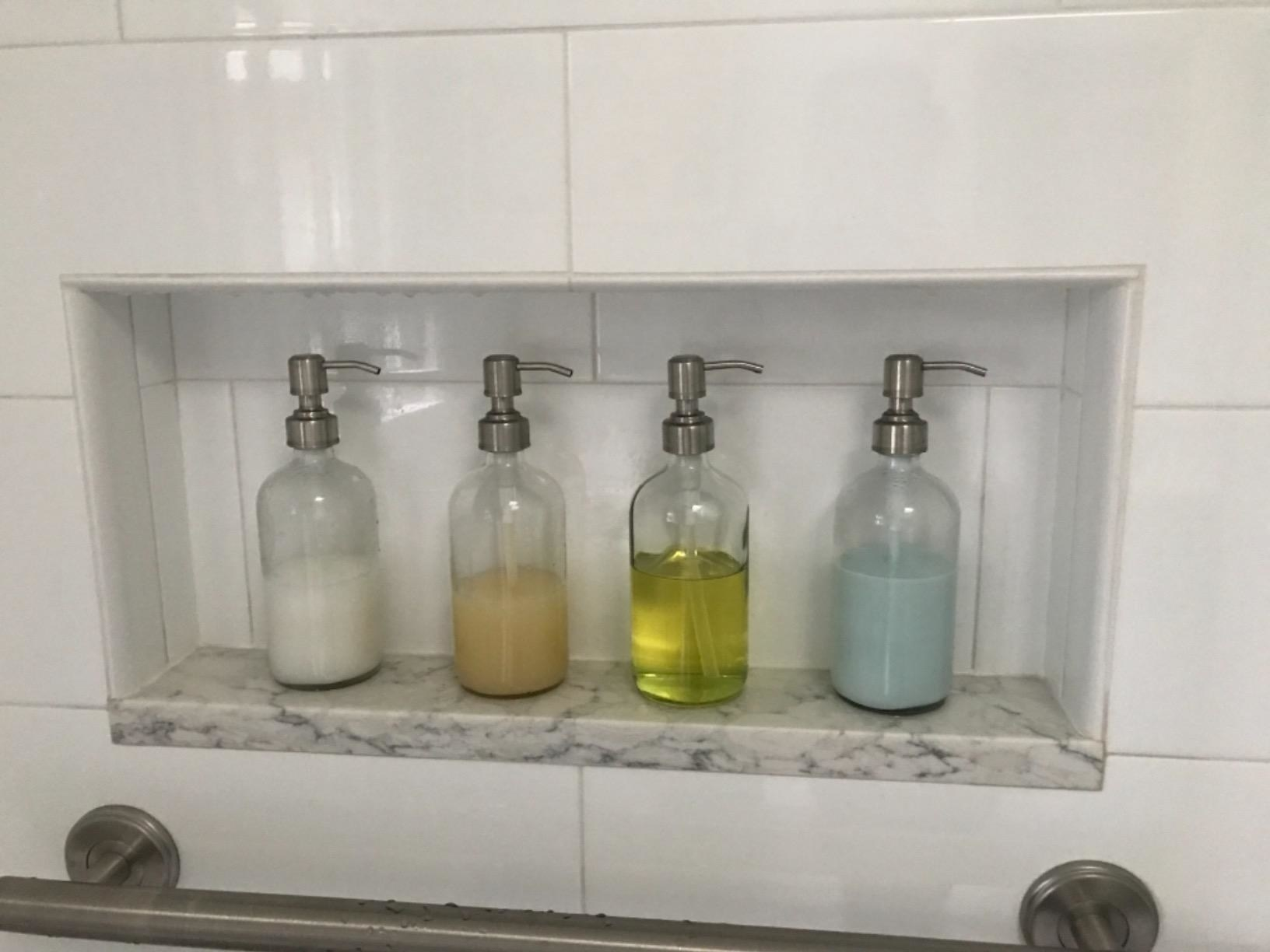 A reviewer photo of four soap dispensers in a shower filled with different liquids