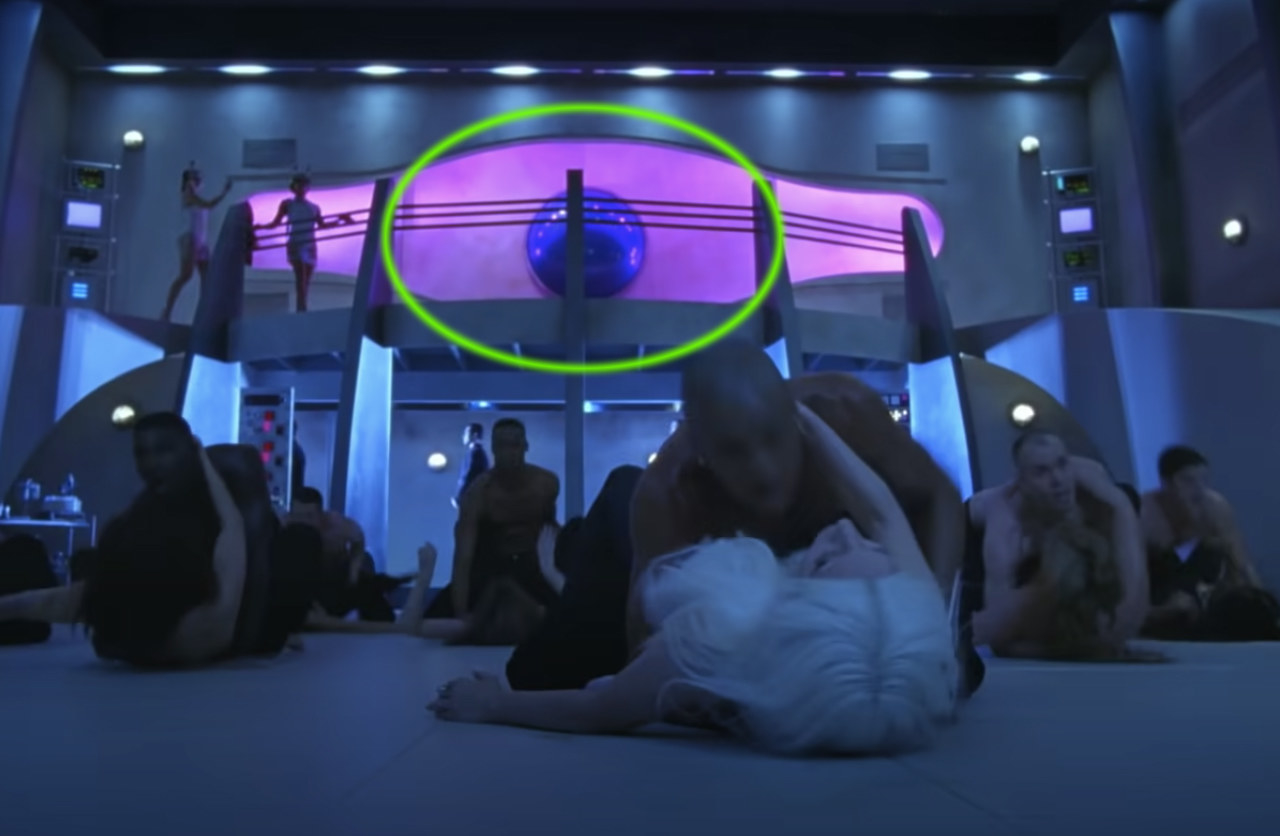 Lady Gaga dances in a lab while a shiny blue sphere hangs in the backround