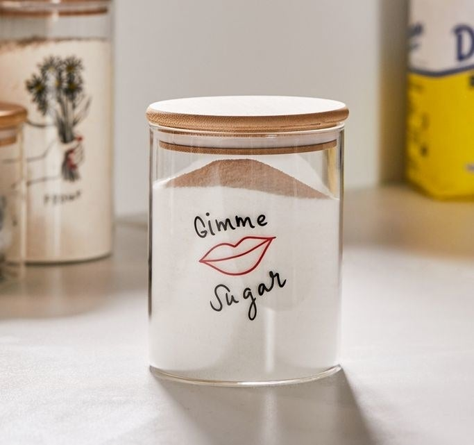 "Clear glass jar with a wood lid and an illustration of lips in red and the words ""Gimme Sugar"" in black above and below it"