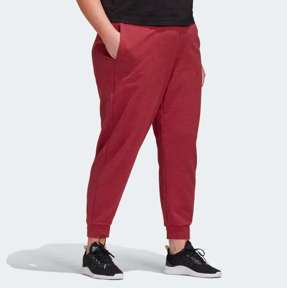 Model wears red Adidas workout pants with black running shoes