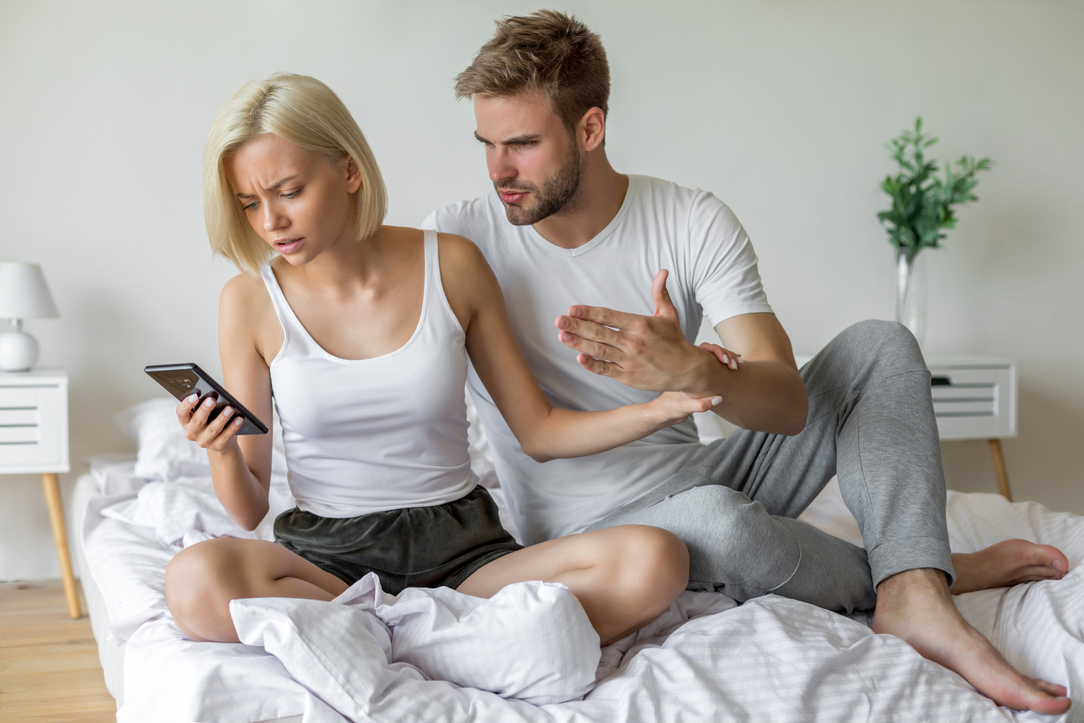 Photo of a couple arguing over a phone in bed