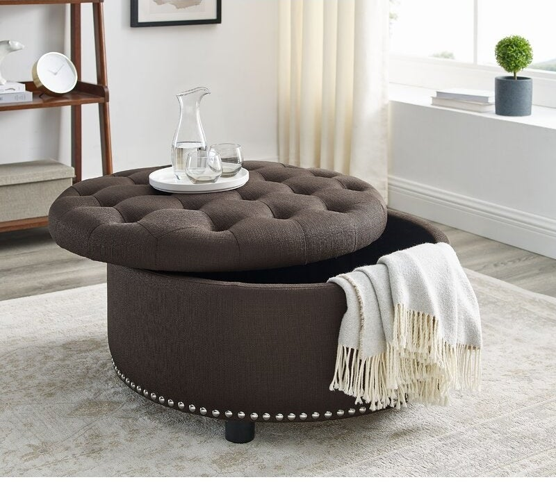 The ottoman is round with silver studs around the bottom trim and a removable tufted top