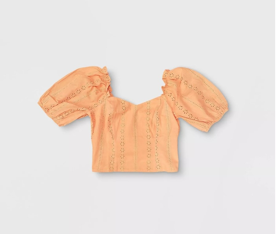 an orange eyelet cropped shirt with puffy sleeves