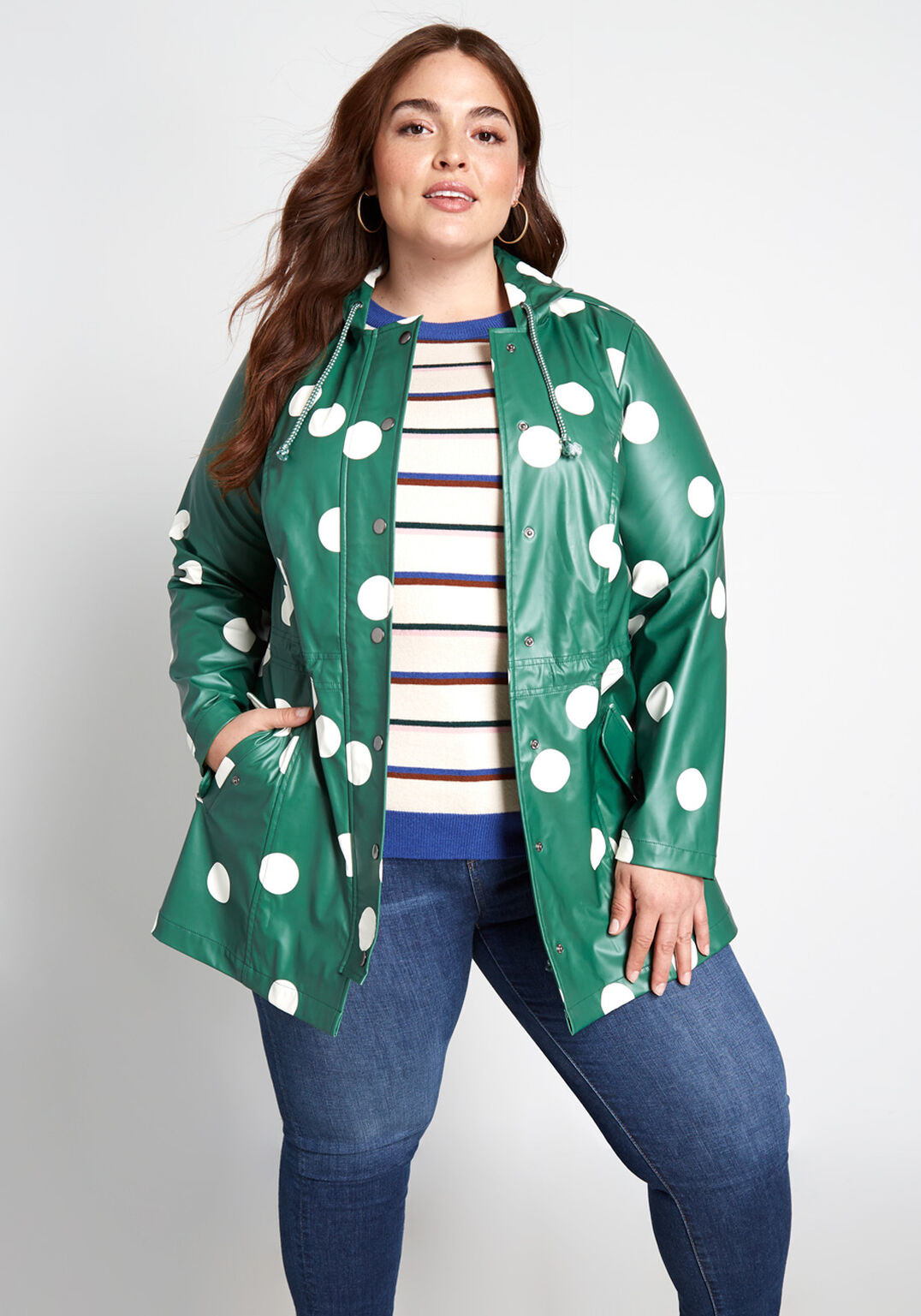 Model wearing green rain coat with large white polkadots throughout