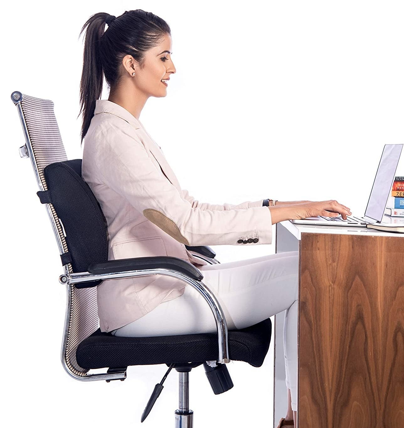A woman using a laptop while sitting on a chair with the back cushion attached to it.