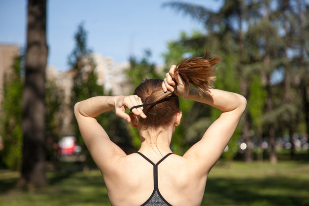 Woman running while pulling her hair into a ponytail