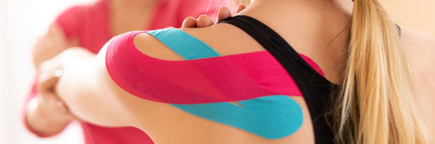 Woman with two different coloured pieces of kinesiology tape gets her arm stretched