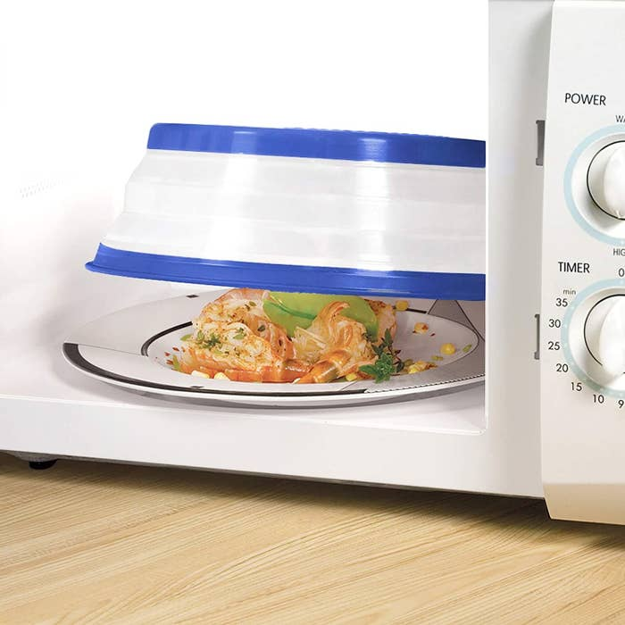 A large silicone bowl is covering a plate of food in the microwave