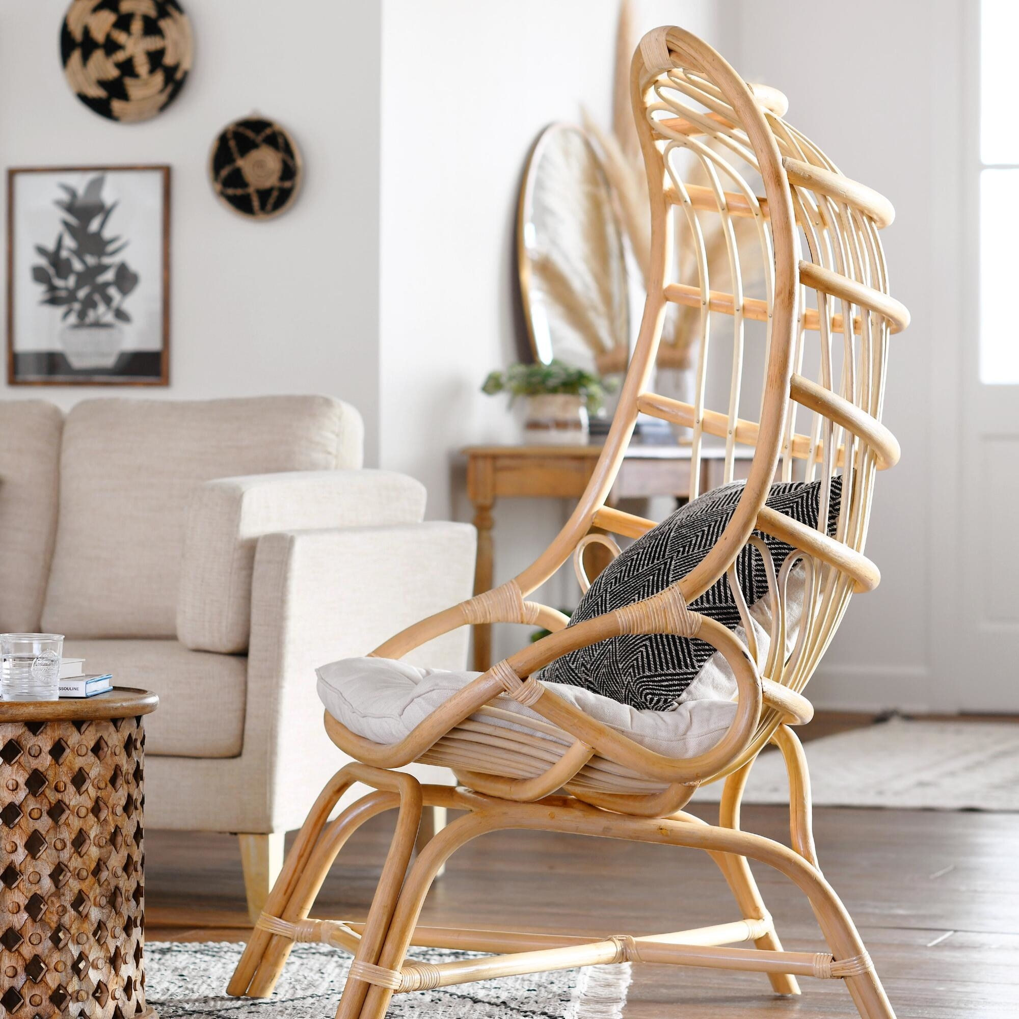 The cocoon chair made out of wood with a curved back design and a cushion and pillow inside