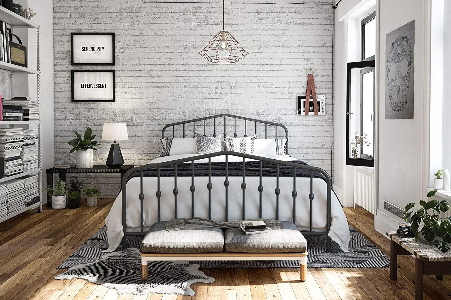 A metal bed frame in dark grey with round finial posts on the headboard and foot board in a bedroom