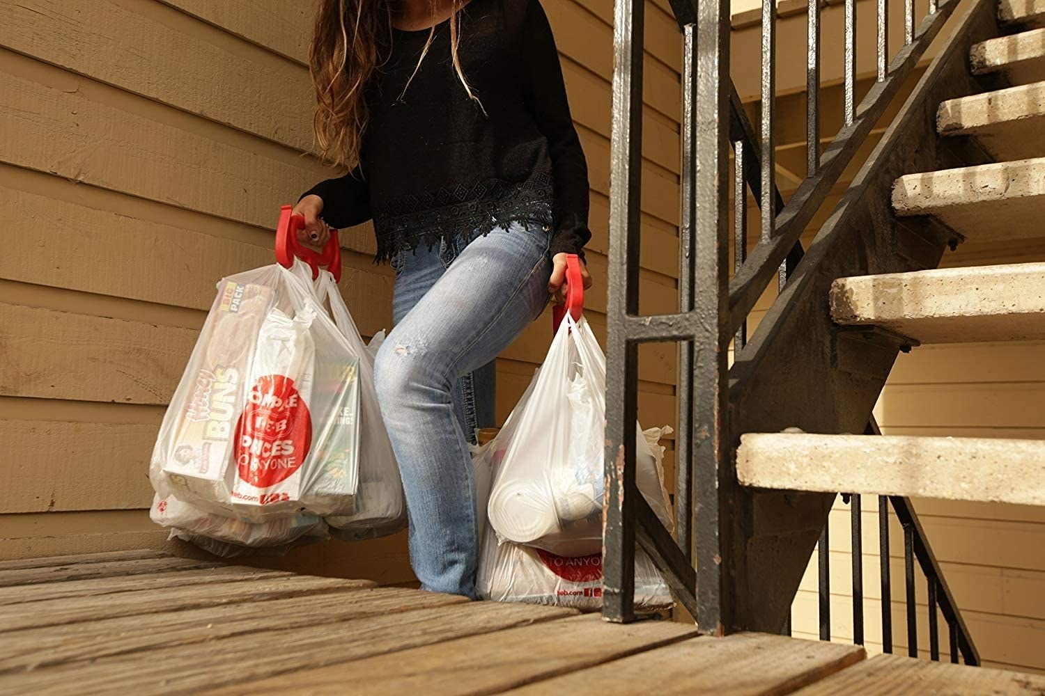 A person holding a thick circular handle in each hand that have multiple grocery bags hanging from them