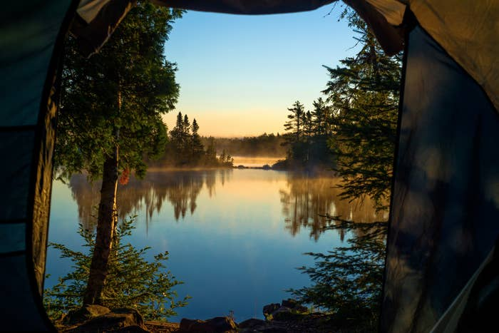 looking out through the doorway of a tent onto morning mist and crescent lake, superior national forest, minnesota