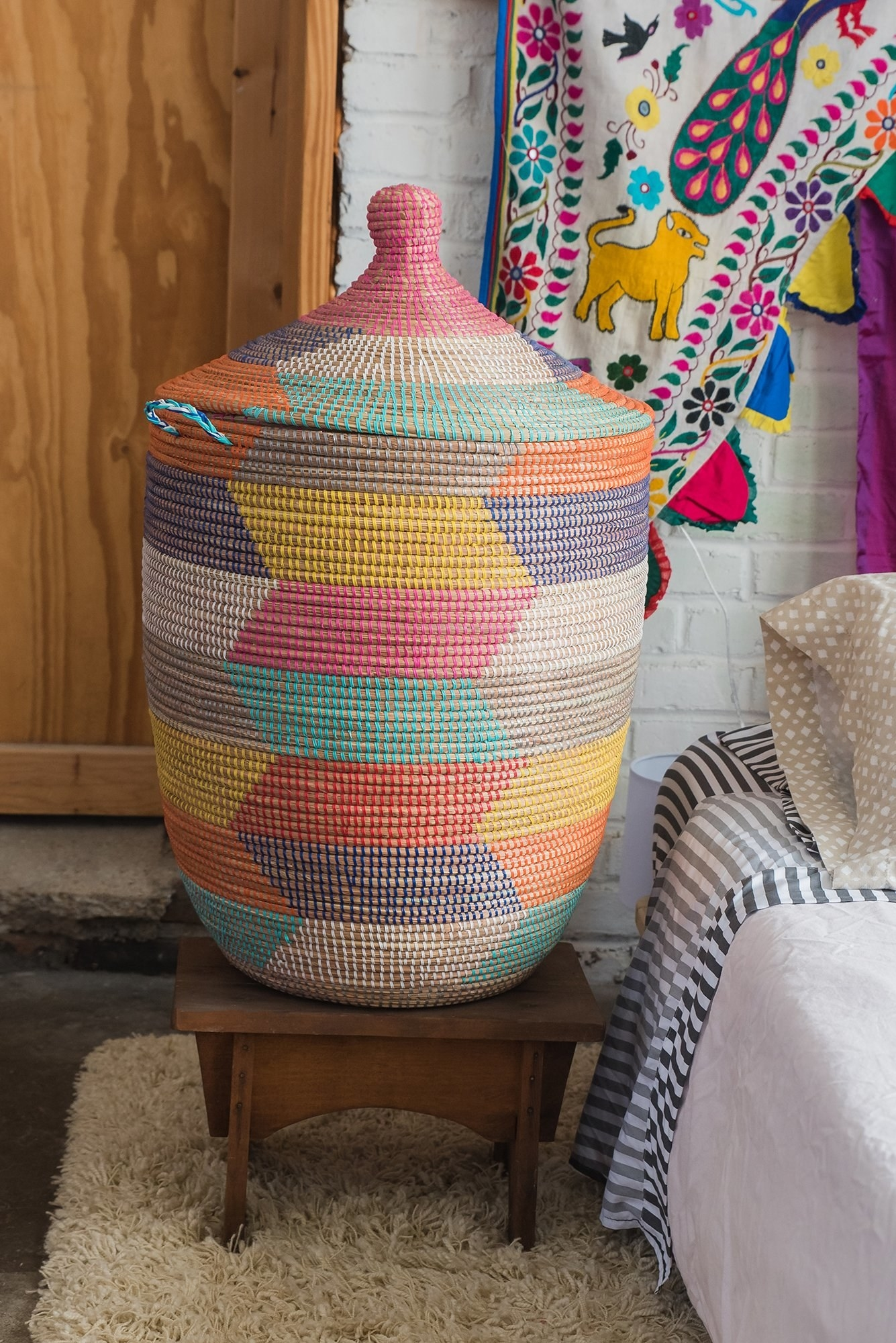 A large woven basket with a lid and handles on the side with patches of different rainbow colors all over