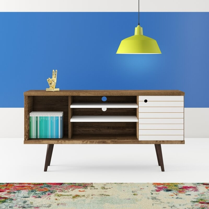 A brown wooden stand with three open shelves and one shelf closed with a white door. it has four brown wooden legs.