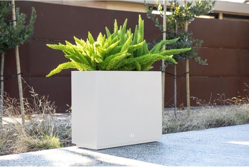 A tall, white rectangular outdoor planter