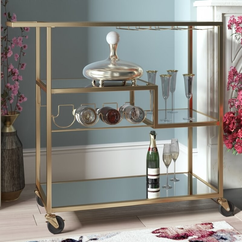 A gold bar cart with three shelves and places to store four wine bottles and hang wine glasses