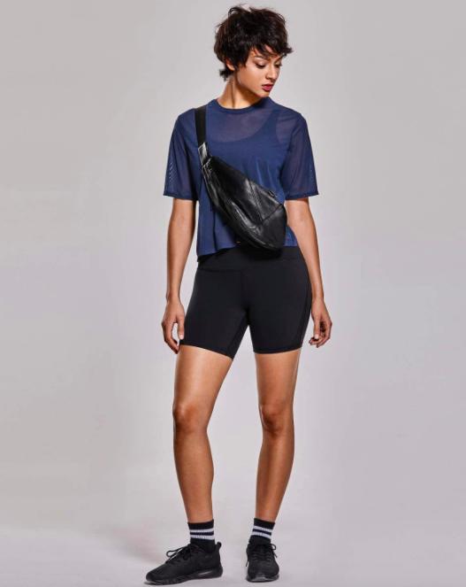 Model wears navy blue mesh workout top over a black sports bra