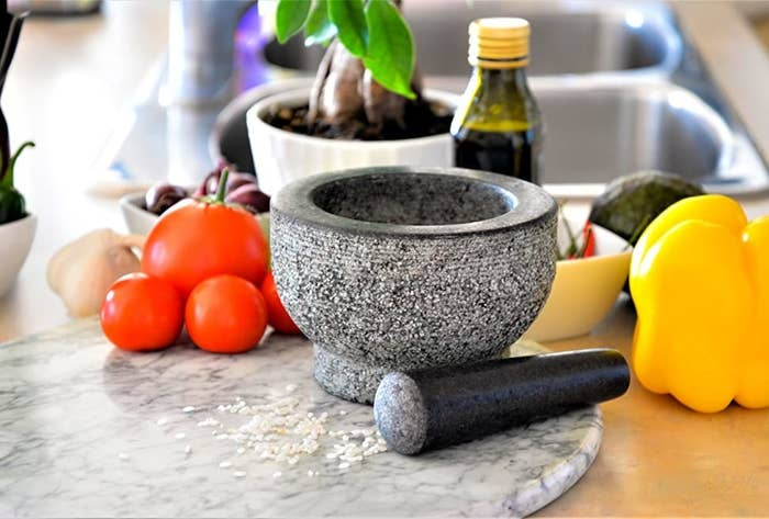 A table with the mortar and pestle surrounded by food items