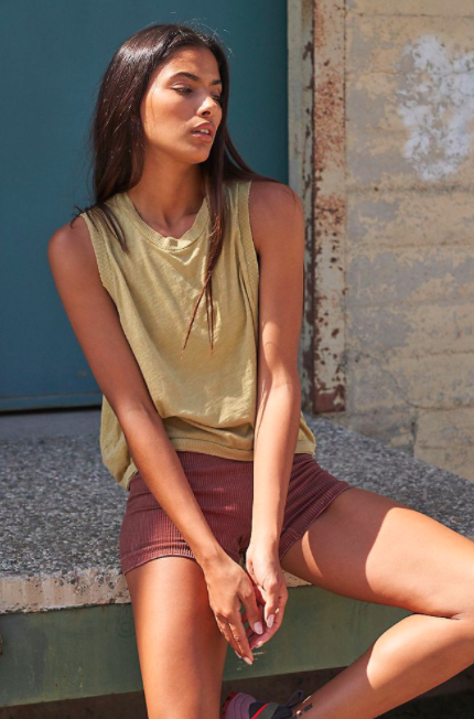 Model wears Free People Movement mustard yellow muscle tank with red shorts