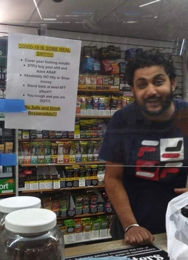 Sign reading COVID-19 is some real shit cover your fucking mouth stfu buy your shit and leave asap stand back at least 6 feet playa you cough and you are out