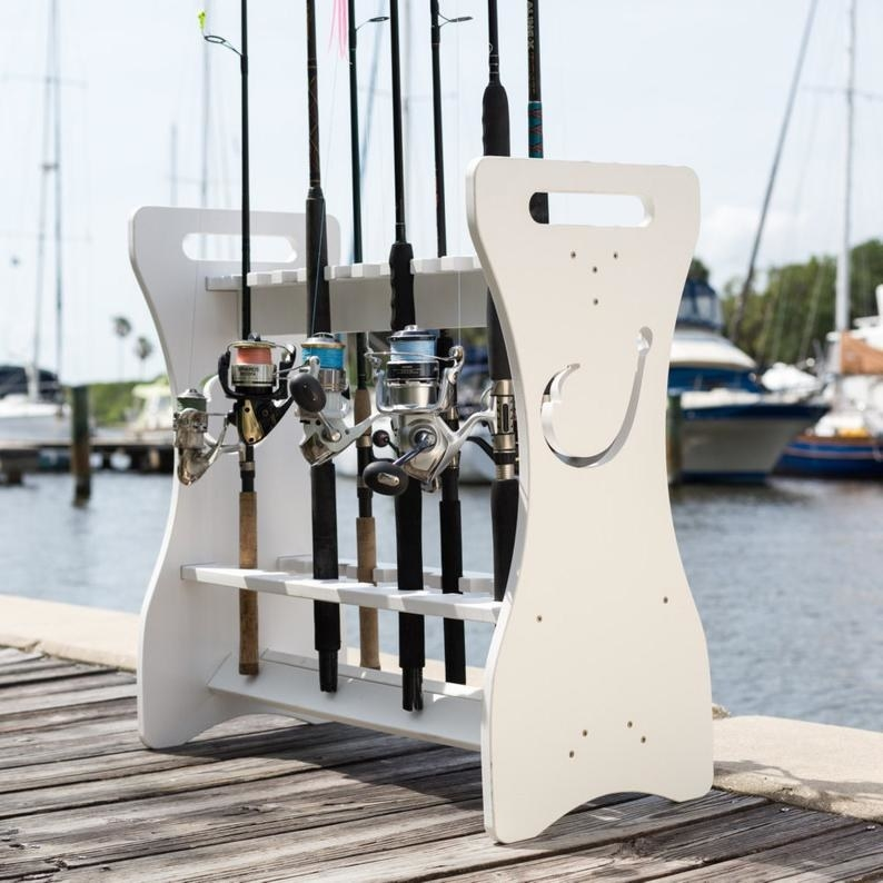 The engraved fishing rod rack sits on a pier holding six fishing rods