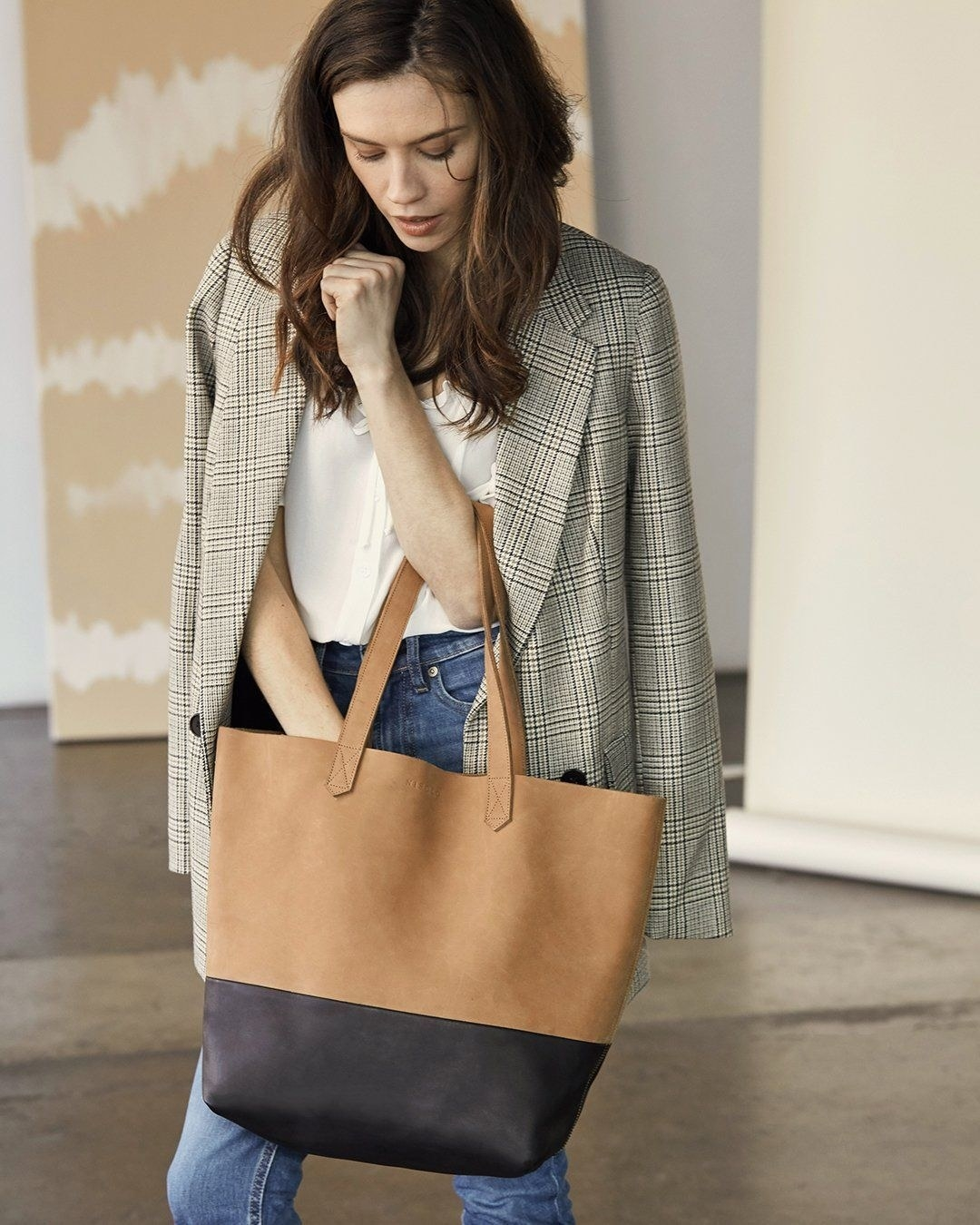 A model carrying the large tan tote with a black bottom panel