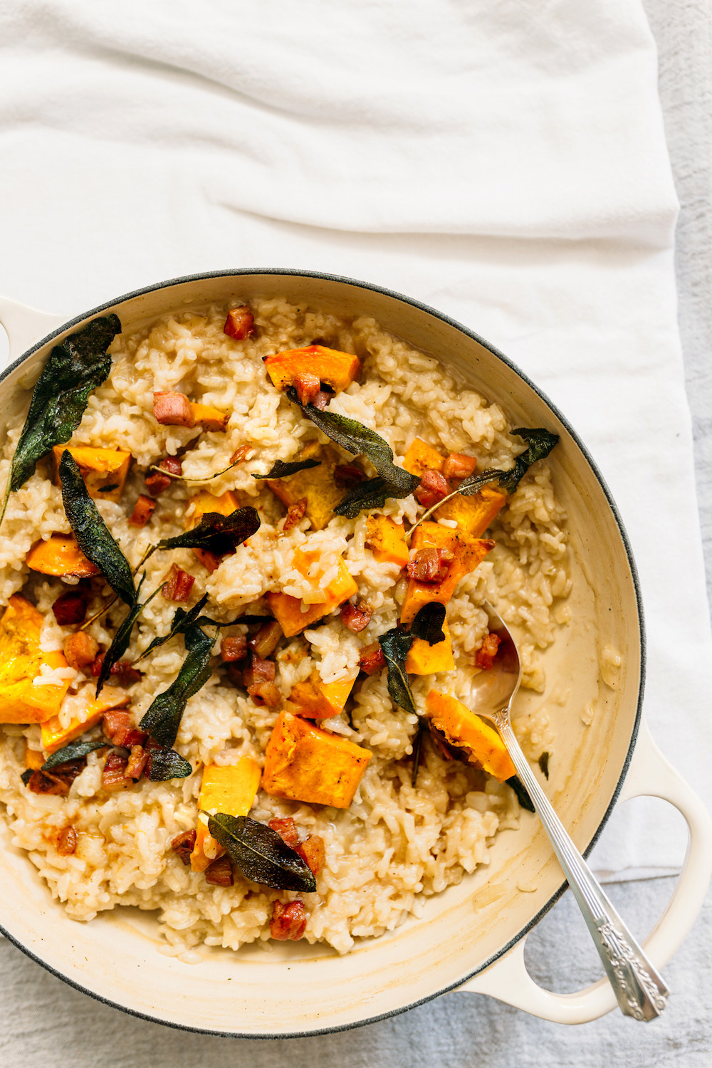 A big pot of cooked risotto with sage leaves, butternut squash, pancetta, and Parmesan cheese.