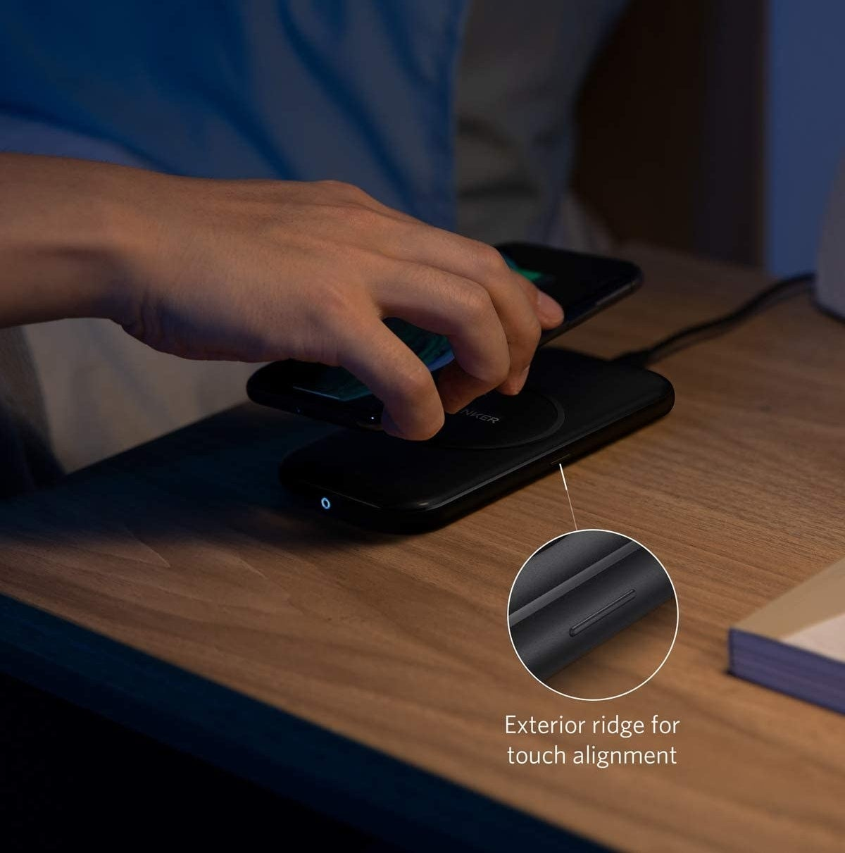 Model's hand putting a phone onto the black rectangle charging pad