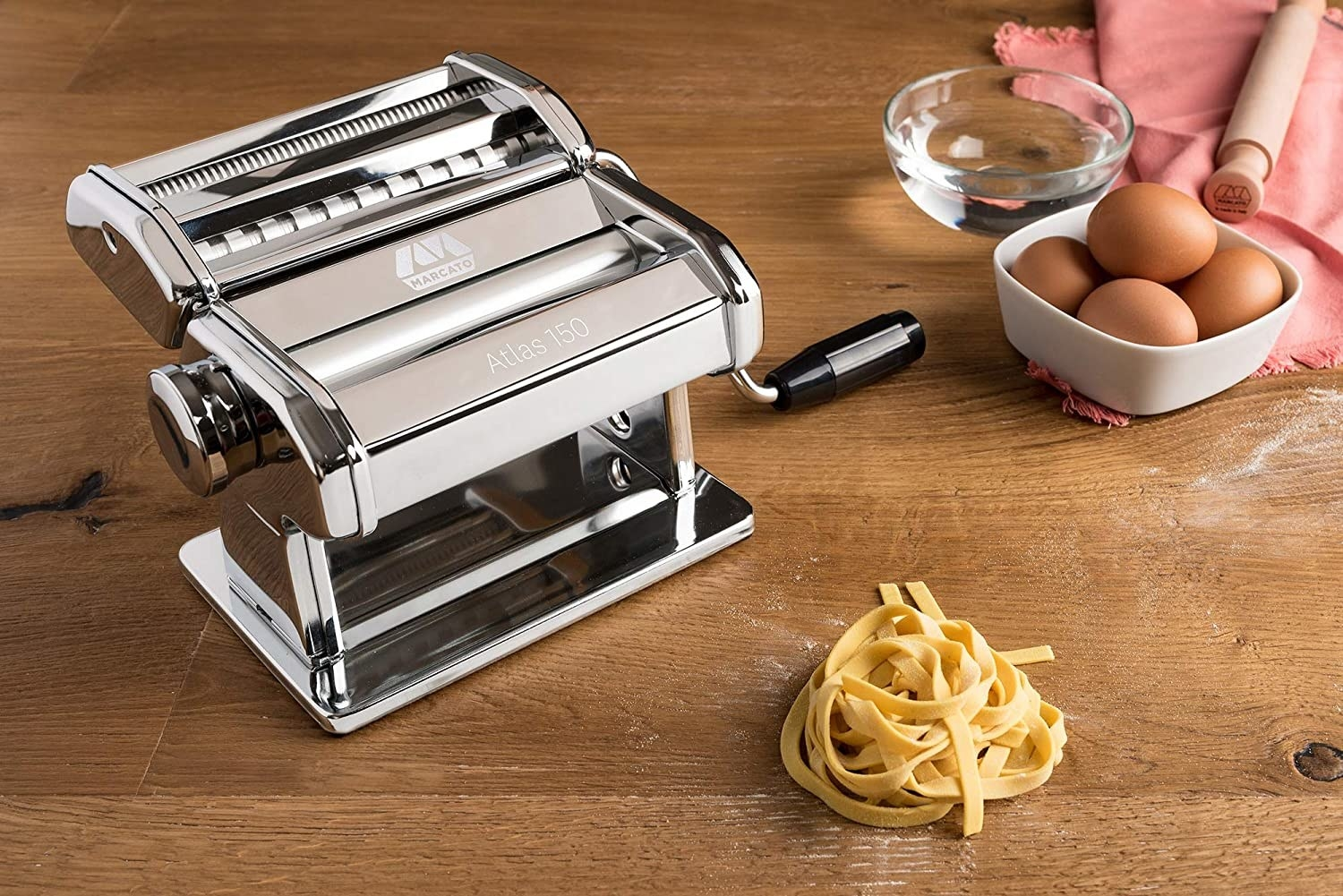 The pasta machine next to a small pile of fresh pasta
