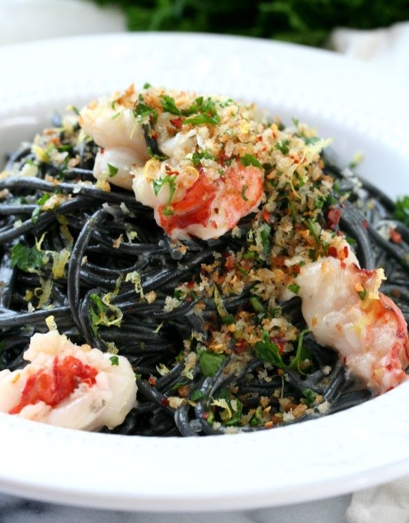 A bowl of squid ink spaghetti with buttery breadcrumbs and lobster meat.