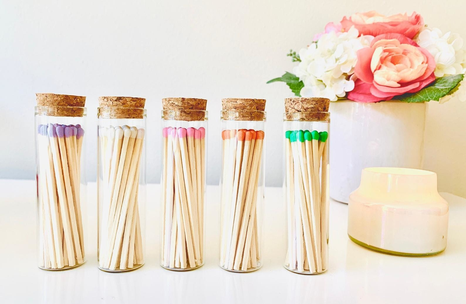 Five tall jars of matches, all with different color tips. The jar is closed by a small cork.