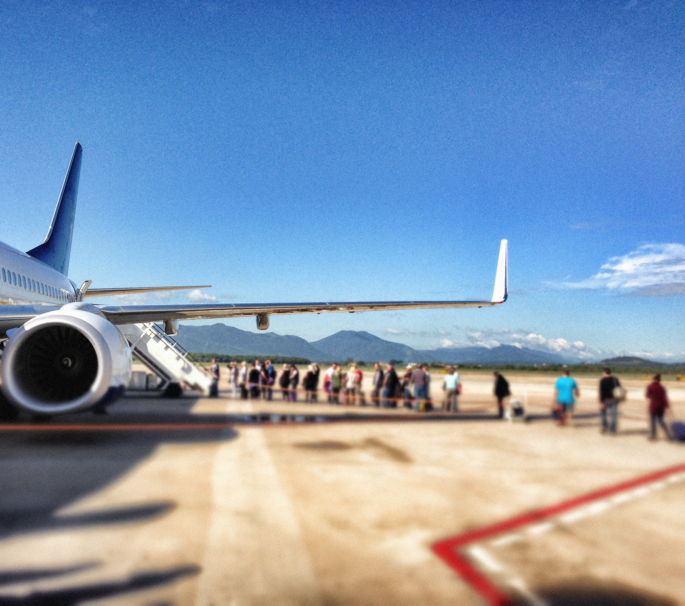 an airplane waiting on the tarmac, mountains in the distance, passengers queuing to board