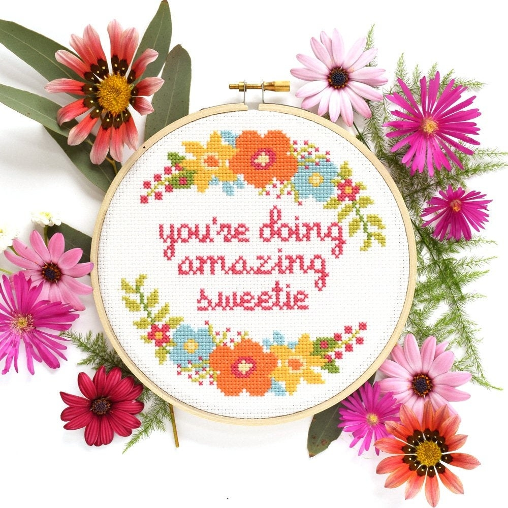 "a cross stitch that says ""you're doing amazing sweetie"" surrounded by flowers"