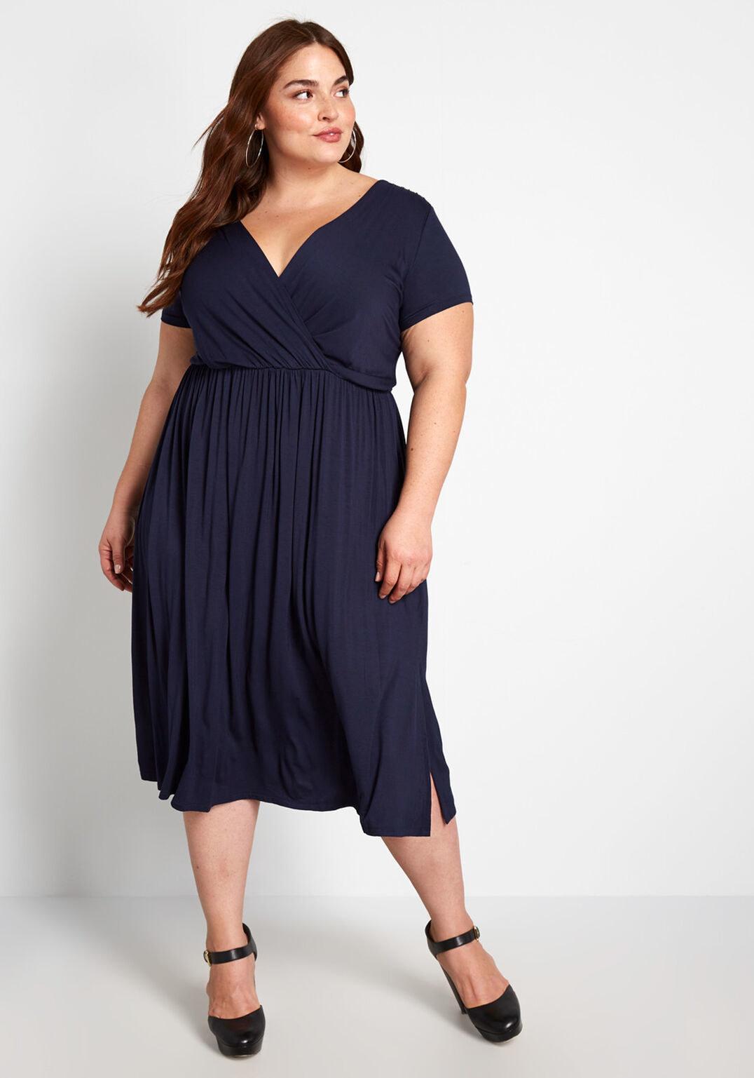model in navy midi V-neck dress with gathered waist
