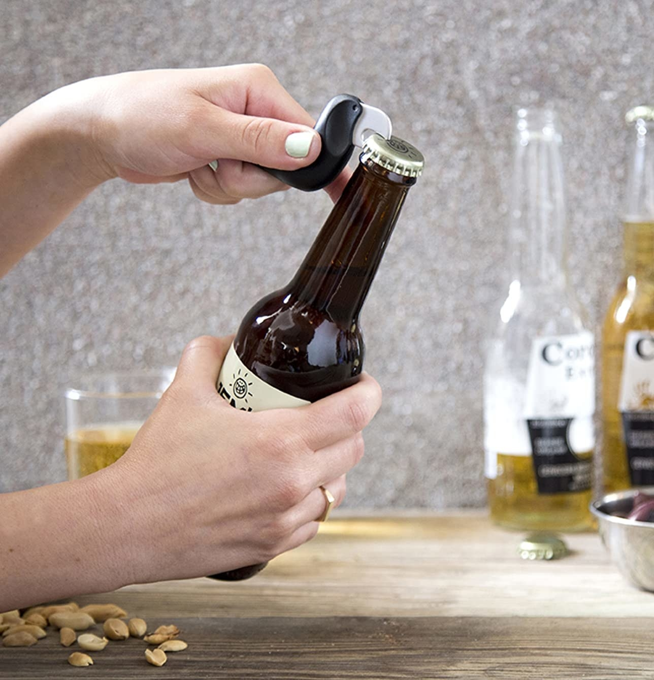 Hand opening beer with the bird-shaped opener