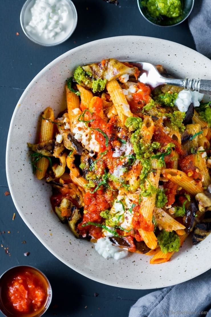 A bowl of penne pasta with eggplant, ricotta, tomato sauce, and pesto.