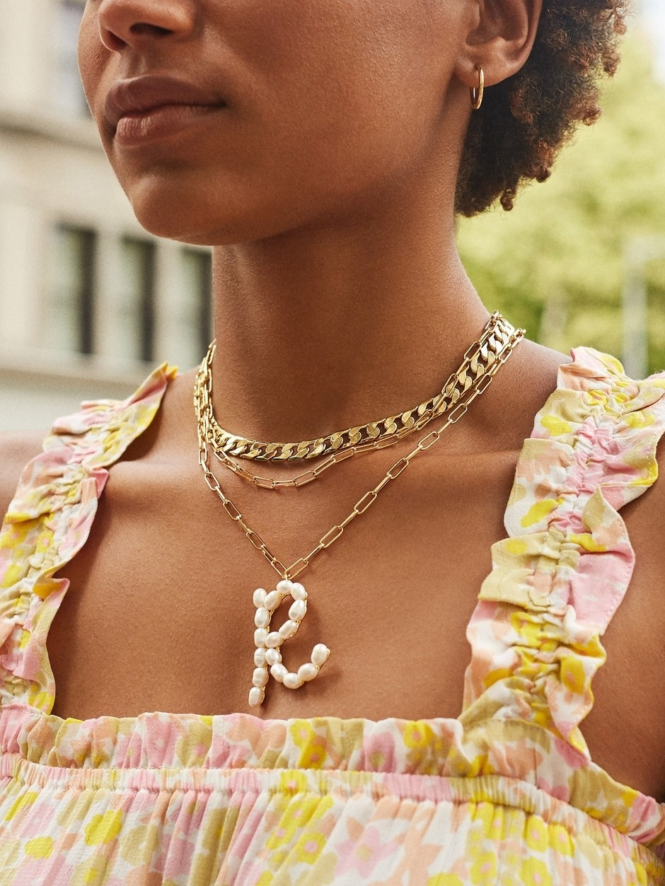 "A model wearing the ""R"" pendant on a gold chain layered with other gold necklaces"