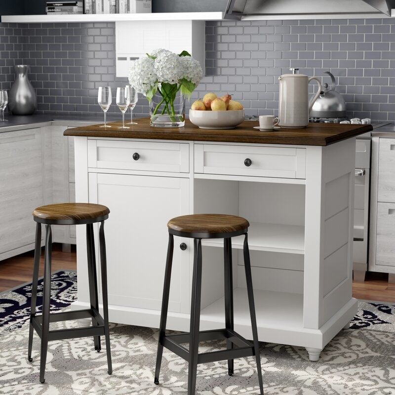 The white island with brown countertop and drawers and a cupboard and a recessed space with a shelf for storage