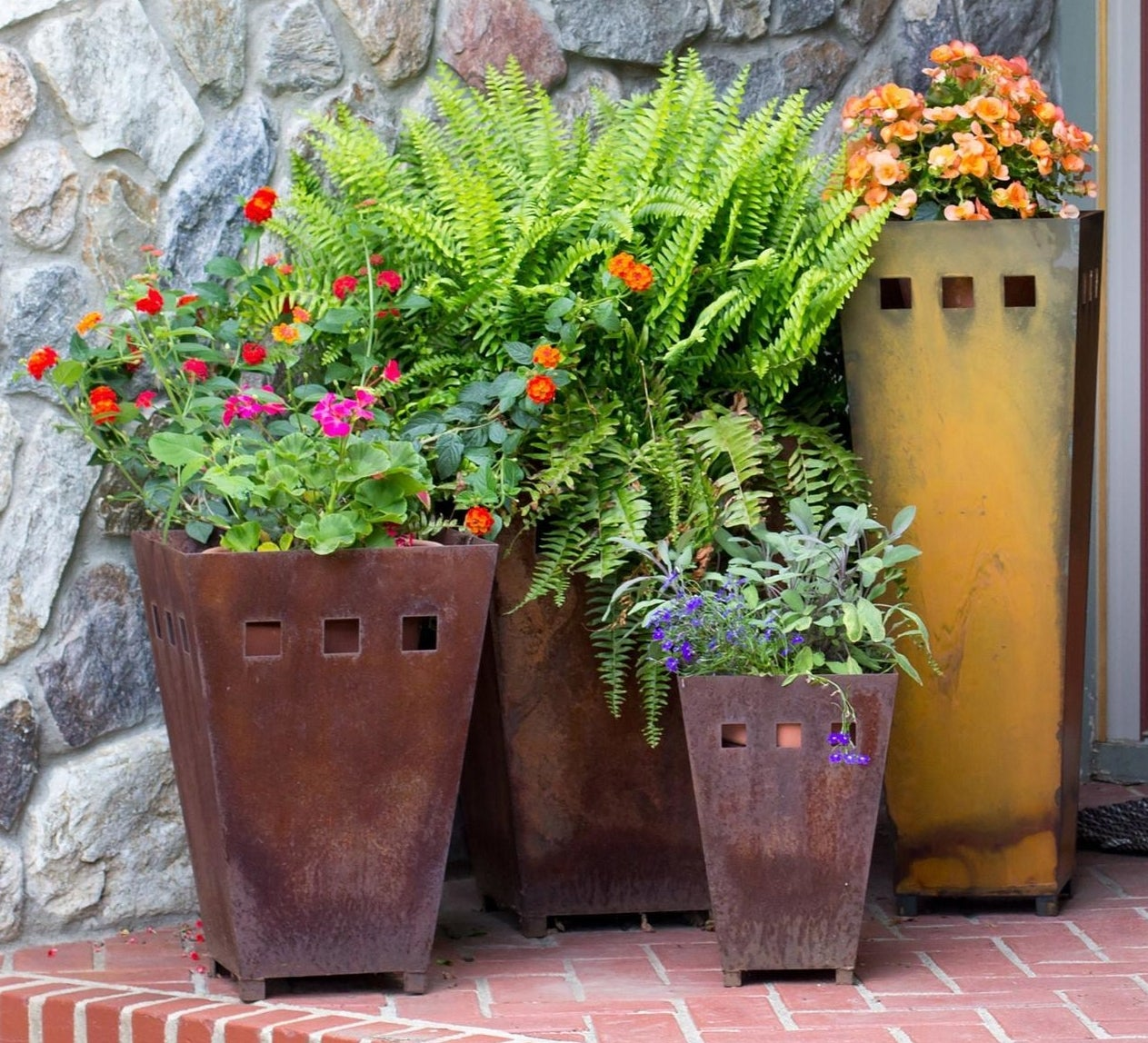 Four different sized, tall trapezoidal rusty metal outdoor planters