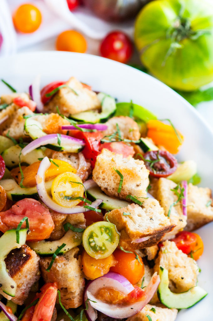 A plate of panzanella salad with colorful tomatoes, red onion, cucumber, and fresh herbs.