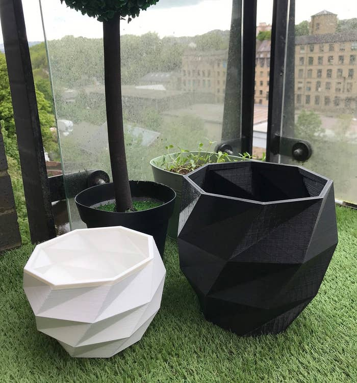 One white and one black 3D-printed planter without any plants inside