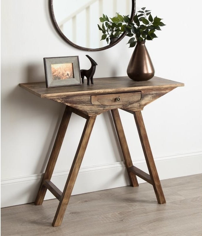 The angular table with a rustic wooden look including one small pull drawer