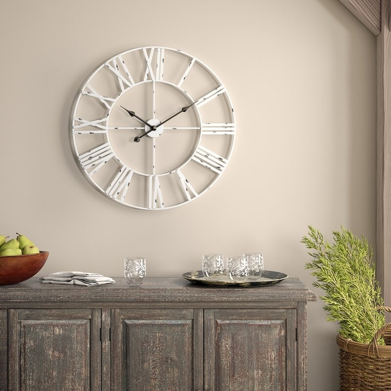 The hollow wall clock with Roman numerals in place of digits and a distressed white finish