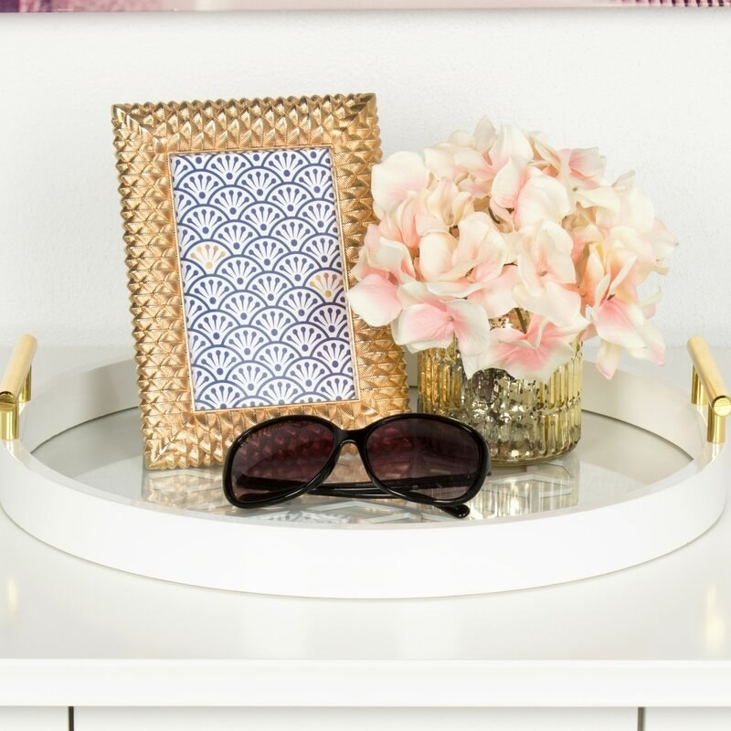 The white circular tray with gold-toned handles holding a photo frame, flowers, and sunglasses