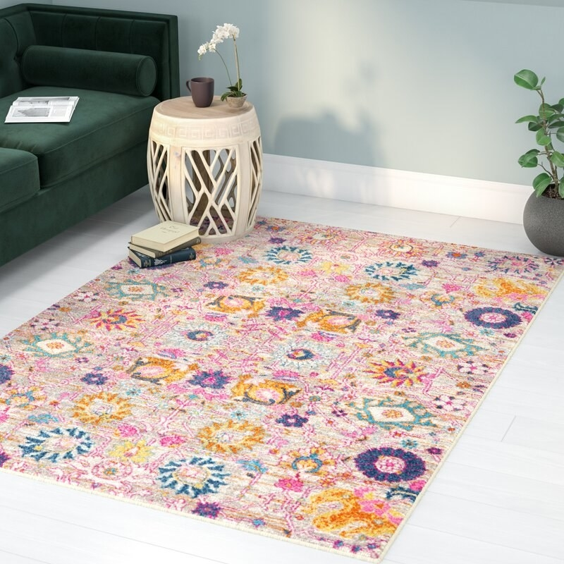 The square-shaped pinkish rug with purple and blue flowers