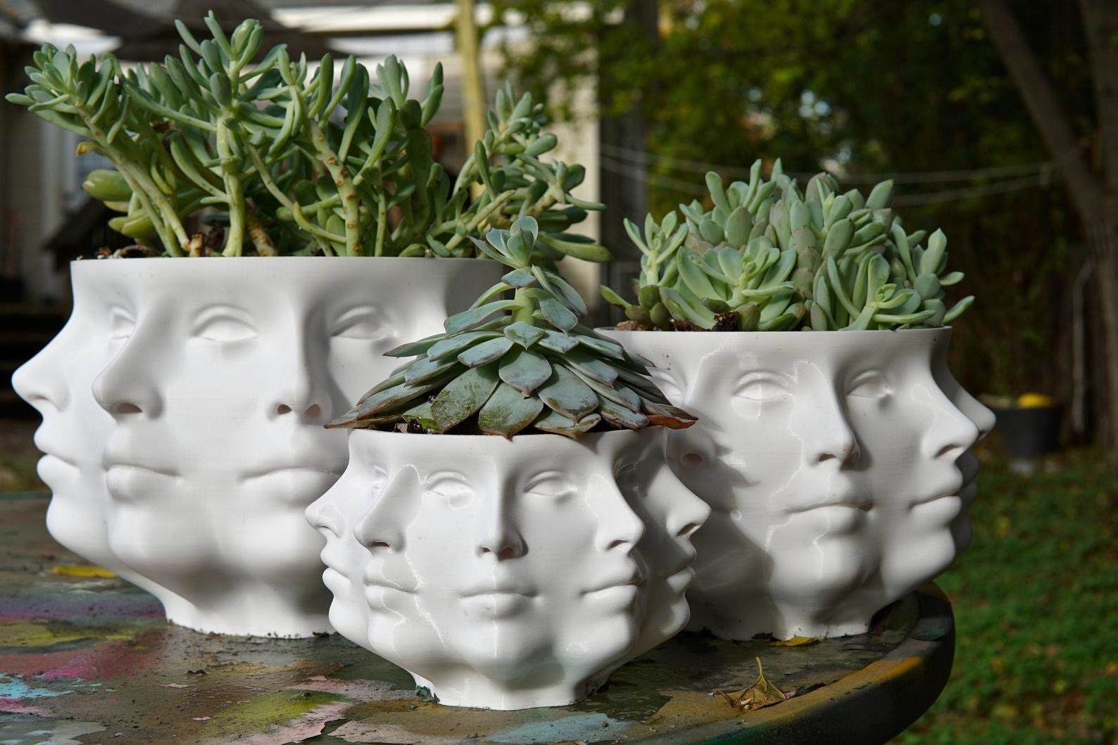 Three different white planters featuring the repeated pattern of a human face