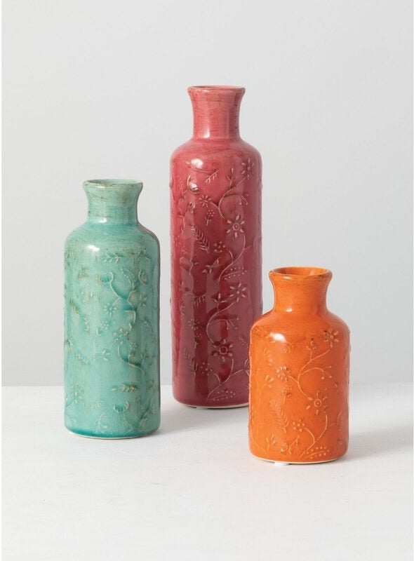 The three vases of different sizes in orange, aqua, and red with a subtle floral pattern