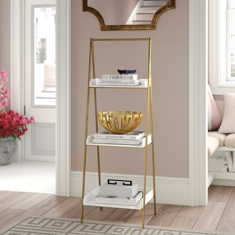 A three-tier bookcase with white, open storage shelves and gold rails holding it up