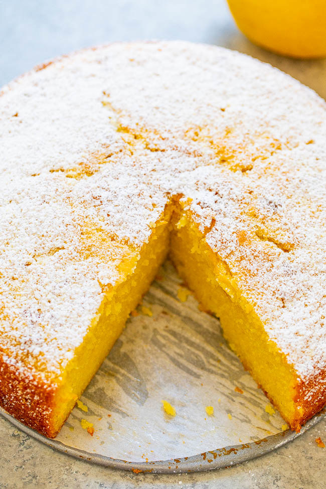 A lemon and olive oil cake with powdered sugar on top and a slice taken out of it.
