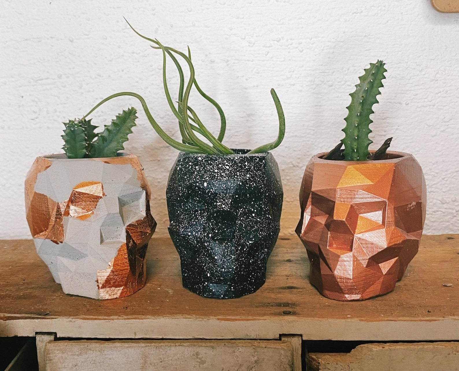 Three different concrete skill planters, one in concrete and gold speckle, one in black speckle, and one in copper
